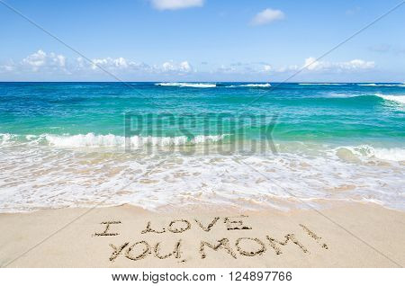 Mother's day background on the sandy beach near ocean sign 'I love you mom