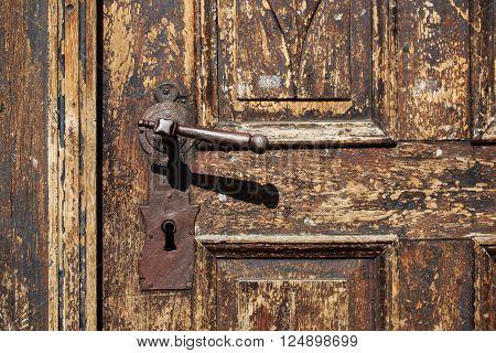 Beautiful old metal door handle with hand on an antique wooden door.