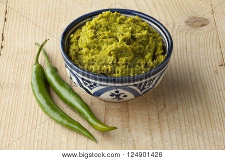 Bowl with green Moroccan harissa and green chili peppers
