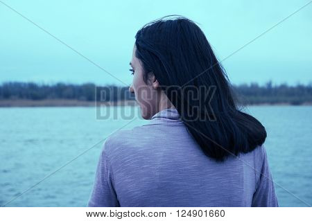 Beautiful young woman is looking at view over the river. Attractive woman enjoys summer rear view.She is admiring beautiful view and enjoying soft sunlight. Instagram-like color filter. Vintage color. Old film imitation.