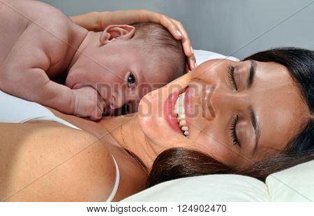 Happy mother lying down on bed with her baby.