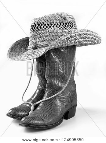 Cowboy boots and straw hat in black and white.