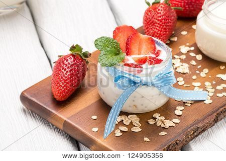 Strawberries desert with cream and cereals served on glass cups over table top.