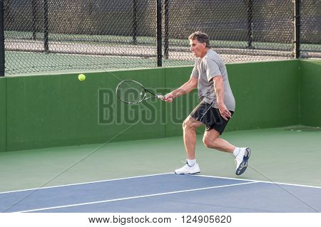 Tall Baby Boomer running to hit a wide forehand.
