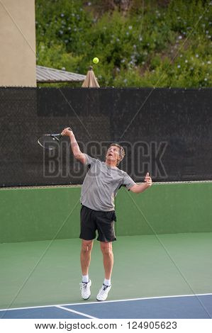 Tall Baby Boomer focused on ball toss in serve.