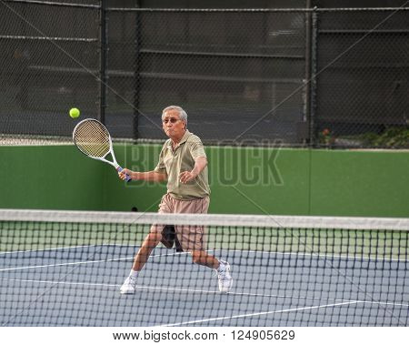 Chinese senior concentrating on the forehand volley.