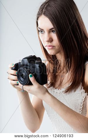 beautiful girl holding a black digital reflex camera