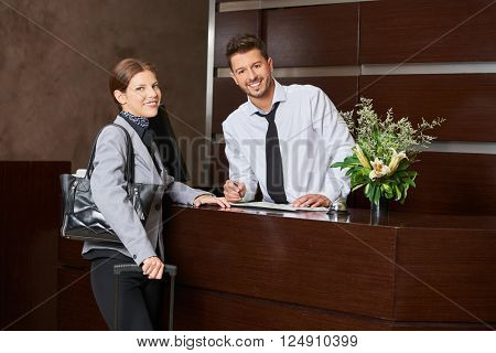 Woman during check-in at hotel reception with receptionist