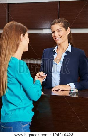 Woman at hotel reception giving key card to female guest during check-in
