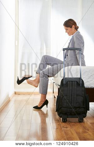 Business woman in hotel room with suitcase taking off her shoes