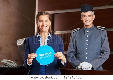 Woman holding service guarantee sign in hotel with smiling concierge behind her