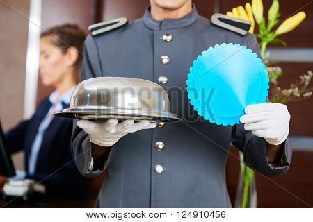Concierge in hotel with advertising badge and tablet in his hands