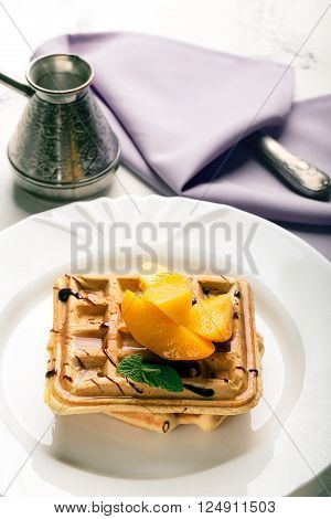 Viennese waffles with peaches and chocolate decorated with mint