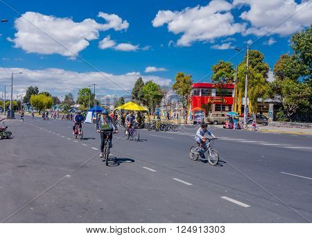 QUITO, ECUADOR - MARZO 23, 2015: Unidentified family used bycicles for their transportation, street closes car passing in a beautiful day