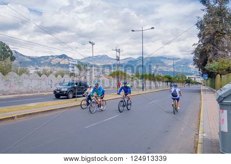 QUITO, ECUADOR - MARZO 23, 2015: Unidentified cyclist doing excercise in the street, road is closed encouraging sports. Mountain on the back, green choice and fresh air