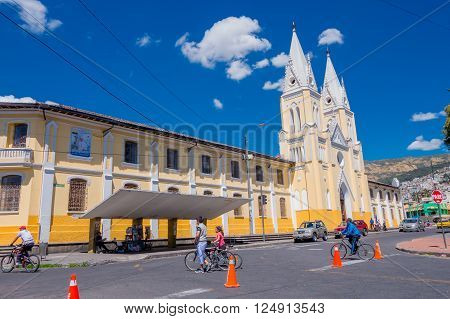 QUITO, ECUADOR - MARZO 23, 2015: Large and imposing church covered by a great sky. Beige and yellow dominated the architecture. Unidientified people crossing with bycicles, sport time