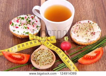 Freshly vegetarian sandwich with cottage cheese, vegetables, alfalfa and radish sprouts, glass of tea and tape measure, slimming healthy lifestyle, food and nutrition