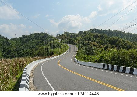 Curve of empty road and green field in country at nan thailand