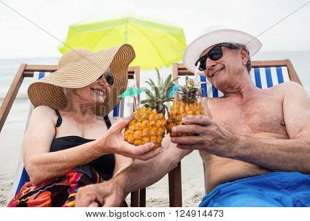 Happy senior couple sitting on deckchairs while toasting pineapple cocktail on the beach