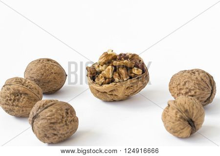 Five walnuts in circle and a half walnut shell full of walnuts. Isolated on white background.