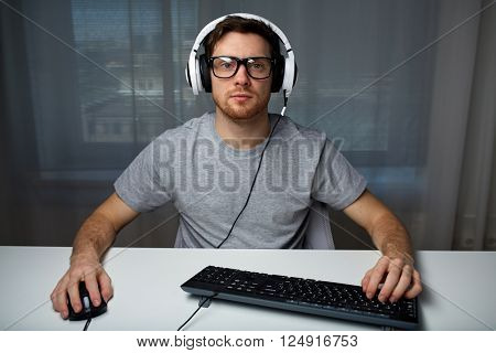 technology, gaming, entertainment, let's play and people concept - young man in headset and eyeglasses with pc computer playing game at home and streaming playthrough or walkthrough video