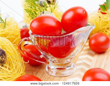 Glass Gravy boat with cherry tomatoes. With Italian pasta nests