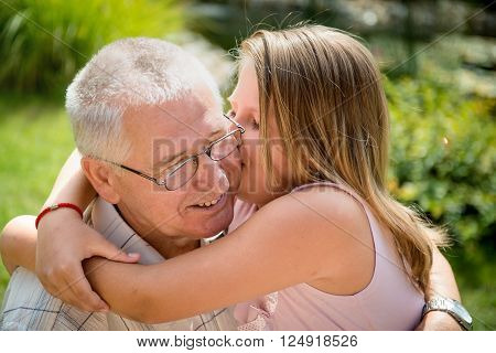 Lifestyle portrait of grandchild kissing grandfather - outside in nature