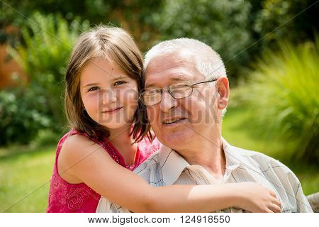 Outdoor lifestyle portrait of grandchild embracing grandfather in nature