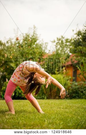 Active childhood - little child exercises outside in backyard