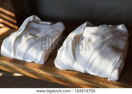 bath, clothes, hygiene and luxury concept - close up of two white bathrobes on wooden shelf at home or hotel