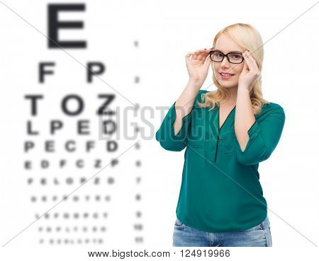 vision, ophthalmology, optics, health care and people concept - smiling young woman with eyeglasses over eye chart background