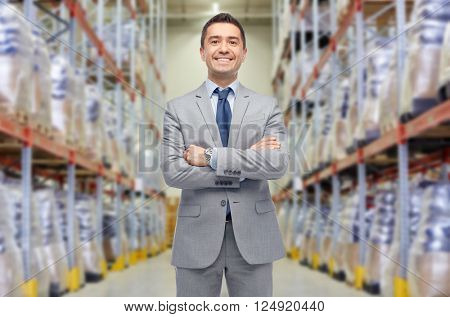 wholesale, logistic, business, export and people concept - happy man in suit and tie at warehouse over warehouse background