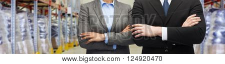 wholesale, logistic, international business, export and people concept - close up of man and woman over warehouse background