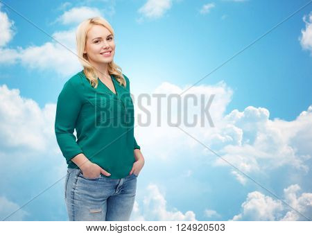 female, gender, portrait, plus size and people concept - smiling young woman in shirt and jeans over blue sky and clouds background