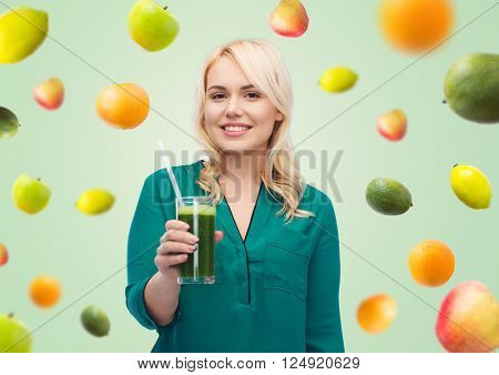 healthy eating, vegetarian food, diet, detox and people concept - smiling young woman drinking green vegetable juice or smoothie from glass
