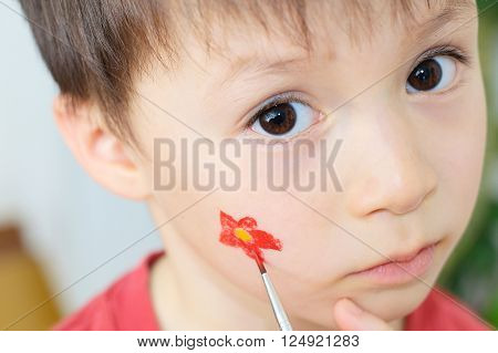 Painting  flower on Caucasian child face looking straight