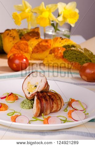 Chicken fillet wrapped in bacon stuffed with cheese on a plate with vegetables Easter bread in the background