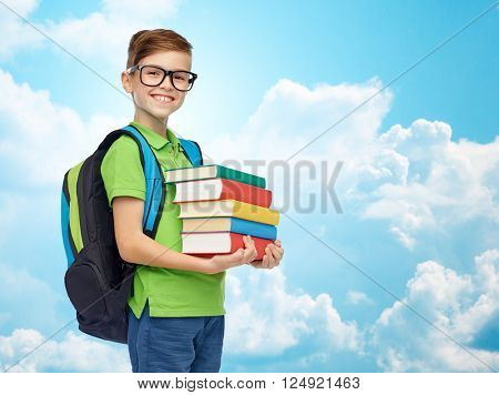 childhood, school, education and people concept - happy smiling student boy in eyeglasses with school bag and books over blue sky and clouds background