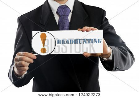 Close up businessman or salesman holding in hands magnifying glass and paper with Headhunting message isolated on white background