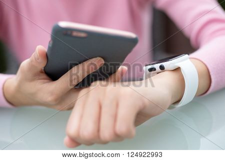 Woman connect with cellphone and smartwatch
