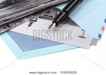 Vintage airmail envelope with a photo and fountain pen over white