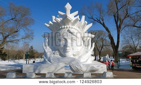 HARBIN CHINA - JANUARY 16 2016: people under a snowy sculpture during the 32nd Harbin Ice Festival. The main attraction is the Harbin Ice and Snow World which covers more than 750000 square meters. Its structures required more than 330000 cubic meters of