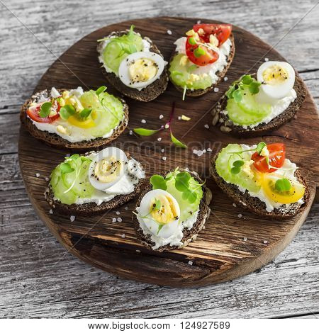 Sandwiches with soft cheese quail eggs cherry tomatoes and celery. Delicious healthy snack or Breakfast. On a wooden rustic board