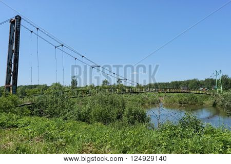 Hanging bridge and small river. Summer landscape