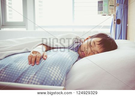 Illness asian boy sleeping on sickbed in hospital with infusion pump intravenous IV drip. Health care and people concept. Vintage style.