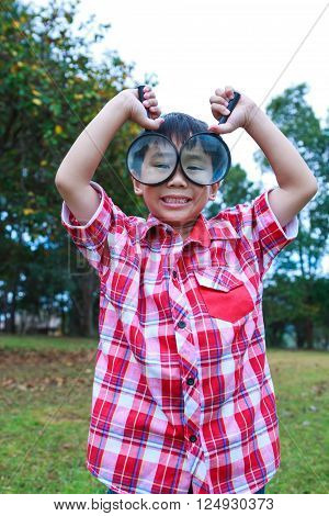 Playful asian child enjoying at park. Young handsome boy peers at the camera through two magnifying glass on blurred nature background. Outdoors in the day time with bright sunlight.
