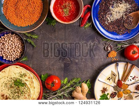 Traditional for asian or eastern cuisine cereal grains beans spices on colorful plates/Lentil rice chick-pea tomato chutney pita. Ingredients for indian or eastern food background/Space for text