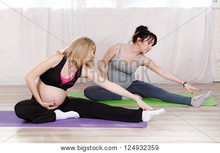 Pregnant cute women,blonde and brunette,dressed in sports attire, perform stretching exercises in prenatal yoga to strengthen the muscles that hold classes in the gym bright in the daytime