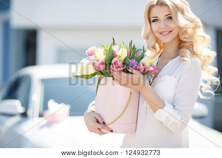 Young beautiful woman with long blonde curly hair and gray eyes,light makeup and a beautiful smile,dressed in a white shirt posing with a bouquet of multicolored tulips near the white car in the summer in the city