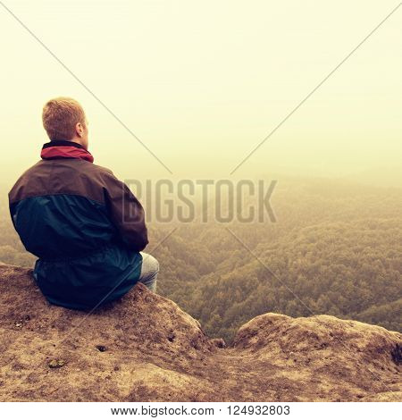 Melancholy And Sad Day. Man At Enge Of Rock Above Deep Vally.  Tourist On The Peak Of Sandstone Rock